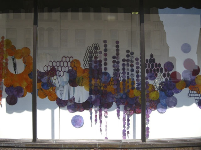 (Installed in the storefronts at 309 Pearl Street, La Crosse, WI.) hand dyed paper circles varying from three to 14 inches,  screenprinting, sewing, cut paper, map tacks Detail from central panel, complete installation spans approximately 32 feet 2012