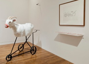 Goat, 2012 Carved goat, glass taxidermy eyes, fabric gag, steel base (fabricated by Aaron Brunner), conceptual Drawing of Animal Conveyor System, 1987 by Temple Grandin (courtesy of the Krannert Art Museum, University of Illinois at Urbana-Champaign), fake security camera, wall text