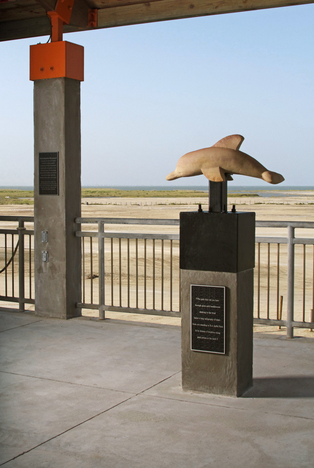 "Pink Dolphin Monument (statue), Dedicated to gender and sexual minority communities in collaboration with writer Sarah Sloane and scientist Frank Pega, made in part with support from the Galveston Artist Residency, Galveston Commission on the Arts, Galveston Park Board of Trustees, and the Pink Dolphin Tavern: Home of the Pink Posse, cement, mixed media, sandstone, steel, and text, 36'' x 16'' x 66'', 2014. The base plaque holds the poem: ""∩ The path that led you here through giant gold headdresses shaking in the wind below a long calligraphy of stars – finds you standing in R.A. Apffel Park lit by dreams of dolphins rising pink arches in the dark ∩"""