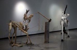 """A Stag and Unicorn In the Forest Go  installation approx. 15' X 7' X 6'4"""" 2013 wood, preserved deer leg, tree trunk, charred tree branch, antlers, axe,  bailing string, bailing wire, coyote ravaged deer skeleton, polyurethane foam,  polystyrene foam, polyurethane adhesive, latex paint, latex acrylic, steel hardware,  chicken wire, concrete, plaster, aluminum fencing wire, horse hair, human hair, goose feathers, gymnasium rope,  tar, machine enamel, spray enamel, oil paint, fabric,  raw hide"""