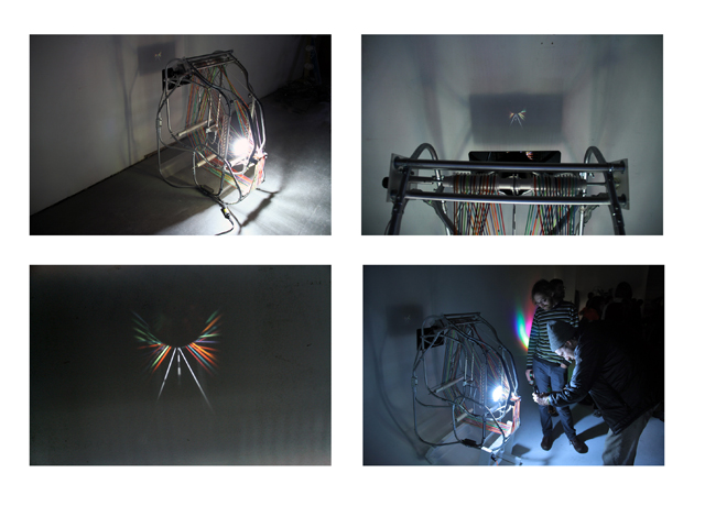 "INFINITAS VIA, (composite image), Electrical conduit, colored elastic, lens, motor, hardware. 28""x40""x40"".  2012"